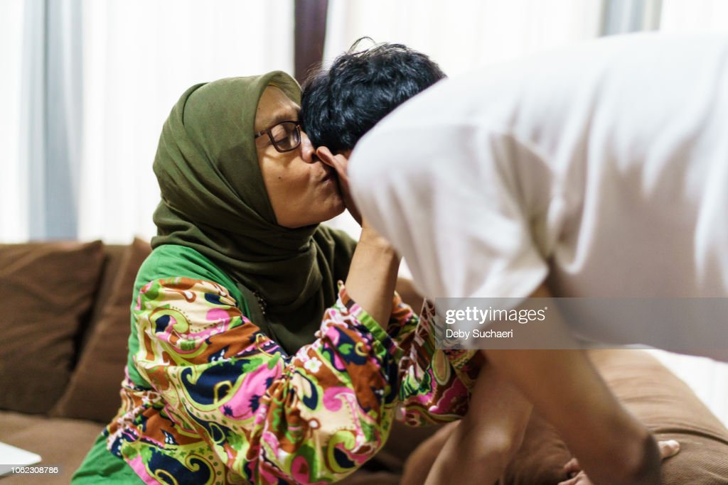 muslim woman with hijab hug and kiss her son : Stock-Foto