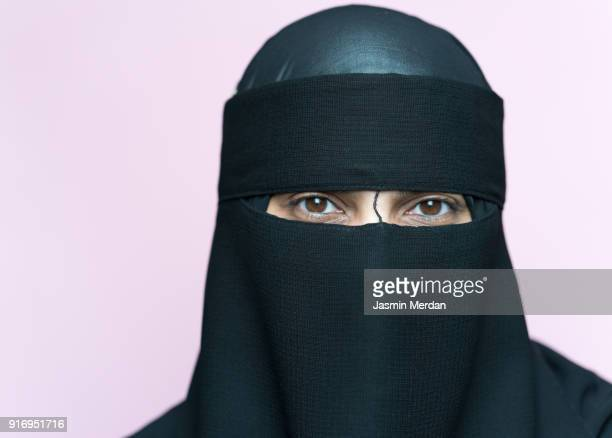muslim woman with traditional black veil - muslim woman darkness stock photos and pictures