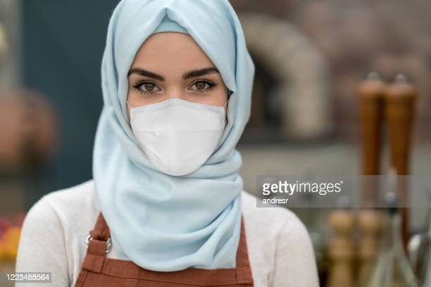 muslim woman working at a restaurant and wearing a facemask - essential services stock pictures, royalty-free photos & images