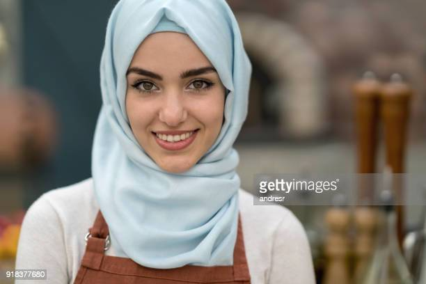 muslim woman working at a restaurant - religious dress stock photos and pictures