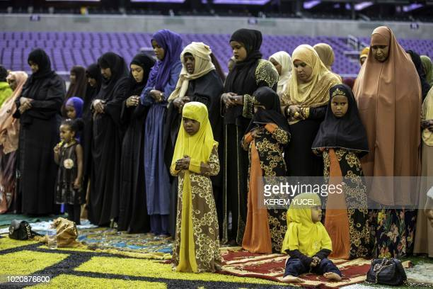 Muslim women and children pray at the US Bank Stadium during Eid alAdha worship services and festivities on August 21 2018 in Minneapolis Minnesota...