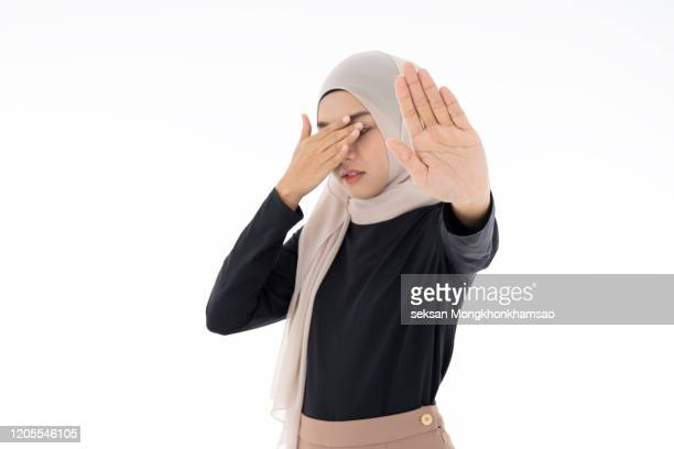 muslim women are signaling a hand to stop violence and pain. - violence stock pictures, royalty-free photos & images