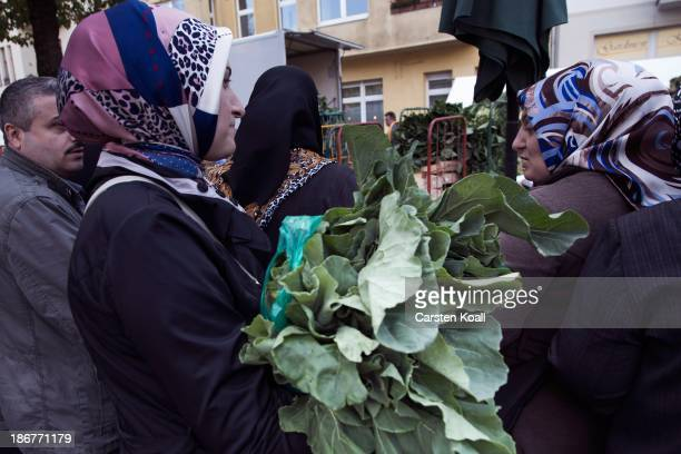 Muslim women buy cabbage leaves at the semiweekly outdoor market at Maybachufer in Kreuzberg district on October 29 2013 in Berlin Germany According...
