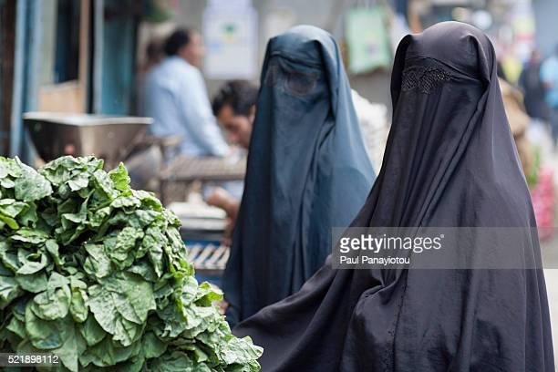 muslim women buying vegetables in the bazaar, srinagar - burka photos et images de collection