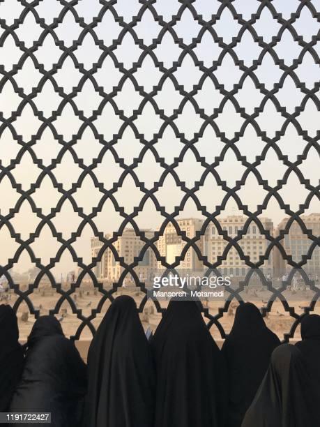 muslim women infront of ancient graves in jannat al baqi cemetery in medina - allah stock-fotos und bilder
