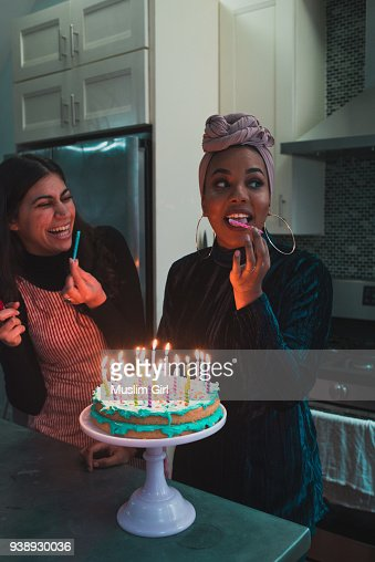 Muslim Women Licking The Candles On A Lit Birthday Cake