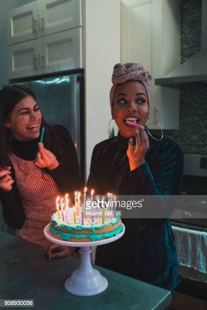 muslim women licking the candles on a lit birthday cake - happy birthday images for sister stock pictures, royalty-free photos & images