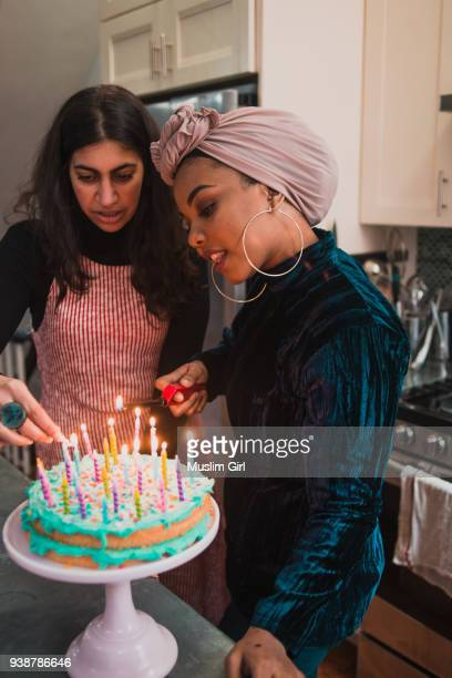 Muslim Women Lighting The Candles On A Birthday Cake