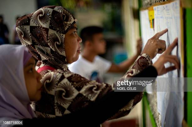 Muslim women look for their names at a voting precinct in Maguindanao on the southern island of Mindanao on January 21 the plebiscite to ratify the...
