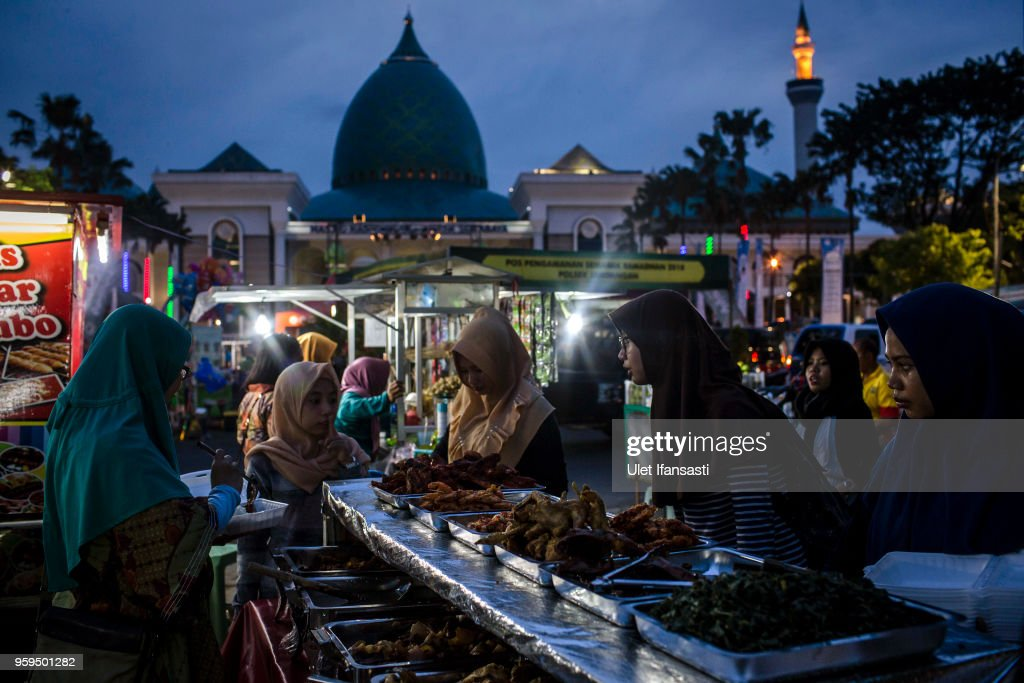 Muslim women looking for food as prepare for iftar on the first day of the holy month of Ramadan at the yard of Grand mosque on May 17, 2018 in Surabaya, Indonesia. Indonesia will begin observing Ramadan on Thursday where millions of Muslims begin the fasting from dawn-to-dusk for a month. For the Islamic State group, Ramadan has become a strategic time to strike as Indonesians faced an uptick of violence linked to the terrorist group during gruesome attacks at three churches and a police station around Surabaya which involved using children as suicide bombers.