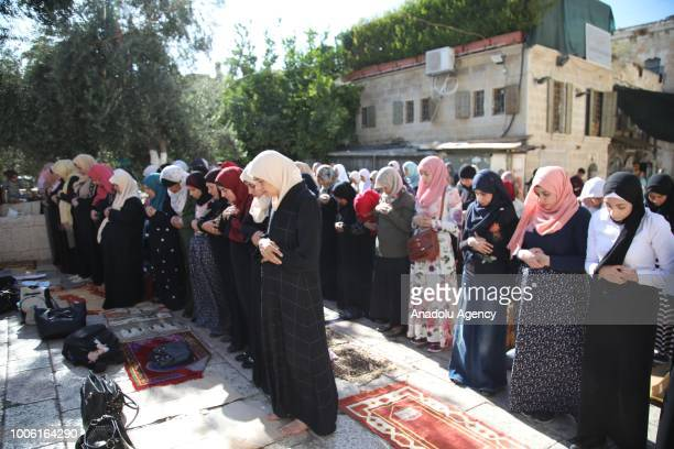 Muslim women perform the afternoon prayer at the Lions' Gate after Israeli forces entered East Jerusalems flashpoint AlAqsa Mosque and began...