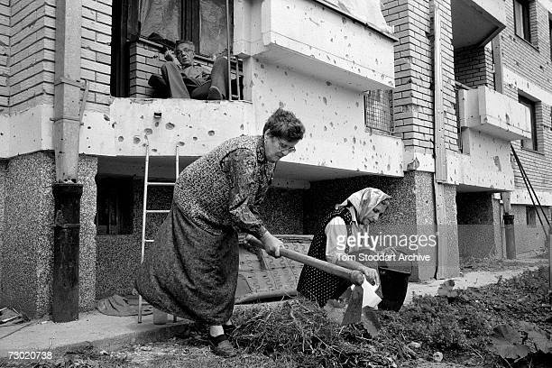Muslim women plant vegetables in a small patch of earth outside their apartment as a man watches, and smokes a cigarette. During the 47 months...