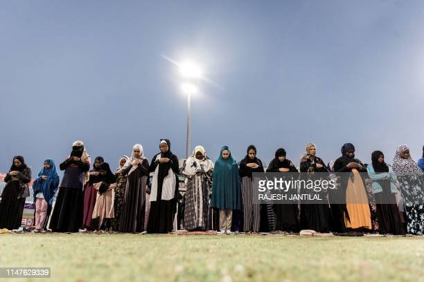 TOPSHOT Muslim women pray on the 27th day of the holy fasting month of Ramadan at the Kingsmead Cricket grounds in Durban at a mass interfaith iftar...