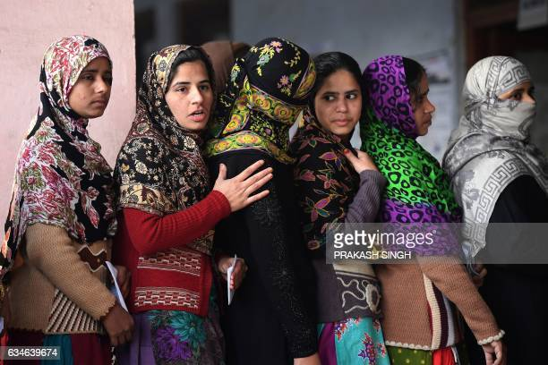 Muslim women queue to cast their votes at a polling station in Muzaffarnagar in Uttar Pradesh on February 11 2017 India's most populous state Uttar...