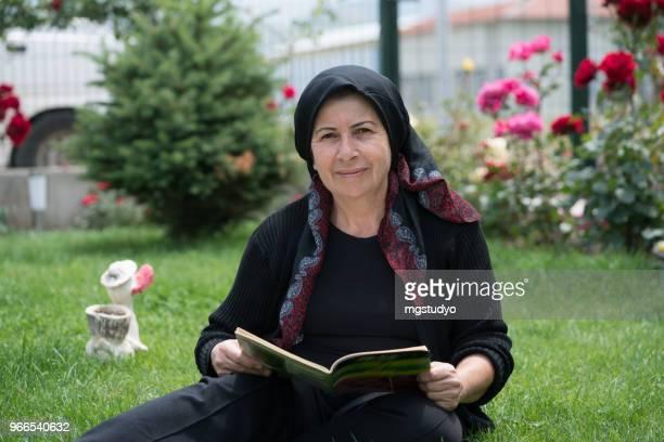 muslimische frauen, die ein buch in der natur - zurückhaltende kleidung stock-fotos und bilder