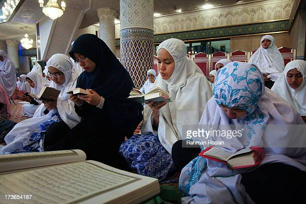 Muslim women recites The Koran while waiting for the night prayer known as Tarawikh to start as millions of Muslims observe the holiday of Ramadhan...