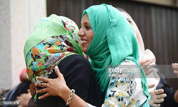 Muslim women say Eid Mubarak as they greet each other after attending prayers at the Regent's Park Mosque on the Eid AlFitr day in London on August...