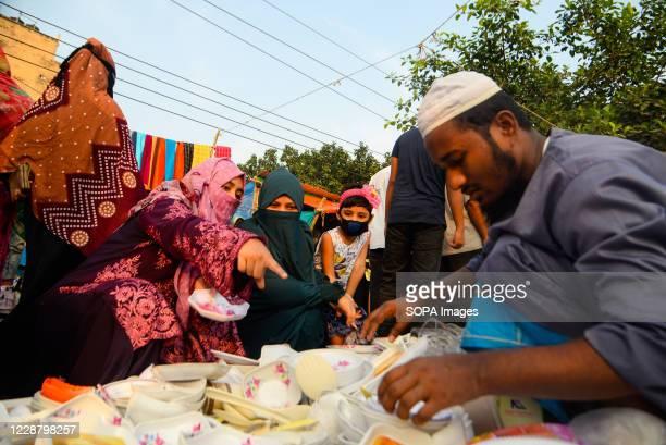 Muslim women seen shopping for utensils on a street in Dhaka.
