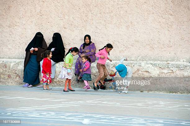 muslim women sitting girls playing morocco - moroccan girls stock photos and pictures