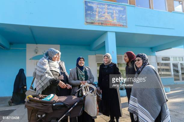 Muslim women stand in front of the Muslim cultural center and mosque following a recent attack just before the beginning of the visit of Aydan Ozoguz...