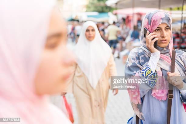 muslim women standing on street using phone - velo fotografías e imágenes de stock