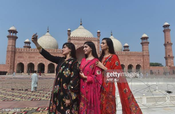 Muslim women take selfie pictures after offering Eid alAdha prayers at the Badshahi Mosque in Lahore on August 12 2019 Muslims around the world are...