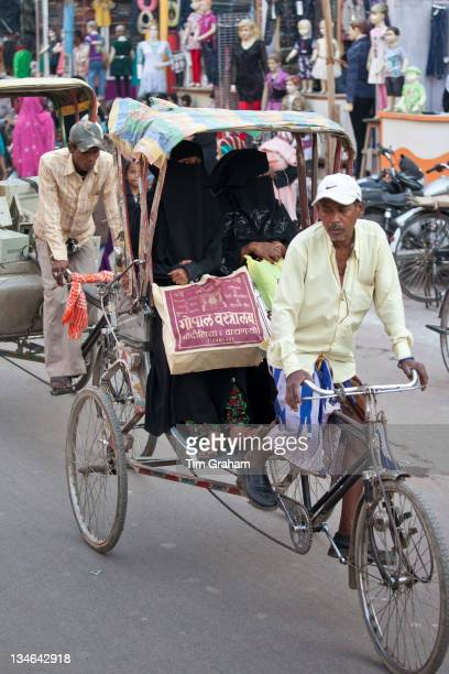 Muslim women travel by rickshaw in crowded street scene in city of Varanasi Benares Northern India