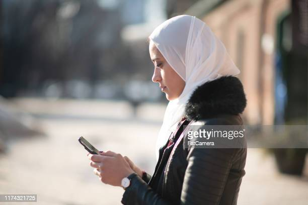 muslimische frauen mit einem mobiltelefon - nordafrikanischer abstammung stock-fotos und bilder