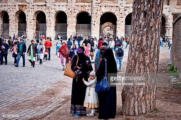 Muslim women wait to take part in prayers in front the Colosseum after municipal police closed three mosques at Centocelle district for the lack of...
