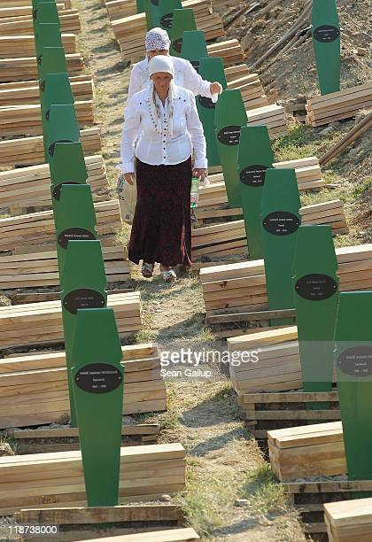 Muslim women walk among open graves in the cemetery of victims of the 1995 Srebrenica massacre the day before the burial of 613 newlyidentified...