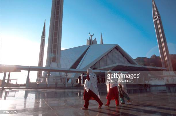 Muslim women walk by the Faisal Mosque February 1 2000 in Islamabad Pakistan The mosque is a gift of the Saudi Arabian government