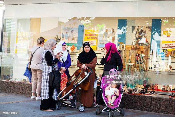 Muslim women with baby buggies and children