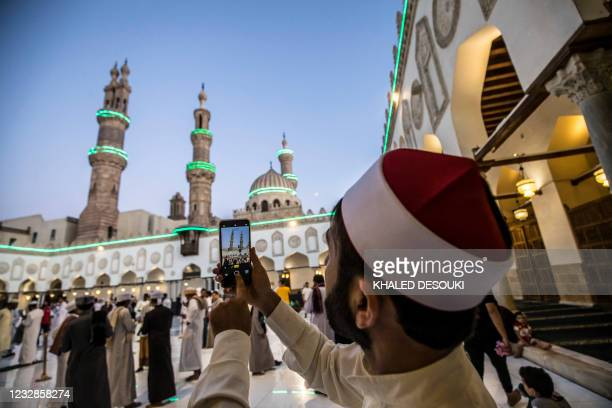Muslim worshipper from Afghanistan takes pictures during Eid al-Fitr prayers, which marks the end of the holy fasting month of Ramadan, at al-Azhar...