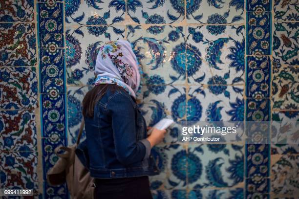 Muslim worshipper prays as she waits to break her fast on June 21 2017 outside the Eyup Sultan mosque on the occasion of Laylat alQadr which falls on...