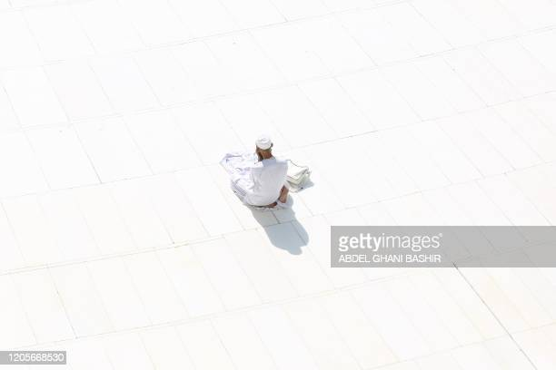 A Muslim worshipper prays near the sacred Kaaba in Mecca's Grand Mosque Islam's holiest site on March 7 2020 Saudi Arabia reopened today the area...