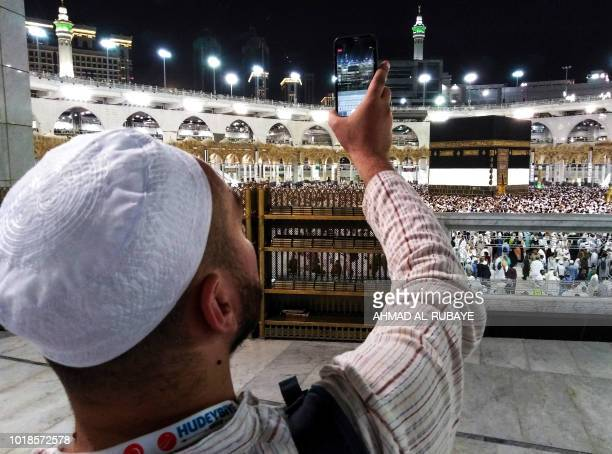 A Muslim worshipper uses his cell phone to livestream film others circumambulating around the Kaaba Islam's holiest shrine at the Grand Mosque in...