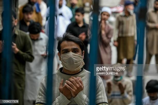 Muslim worshipper wearing a facemask prays during Friday prayers outside the closed gate of Jamia Mosque during a government-imposed nationwide...