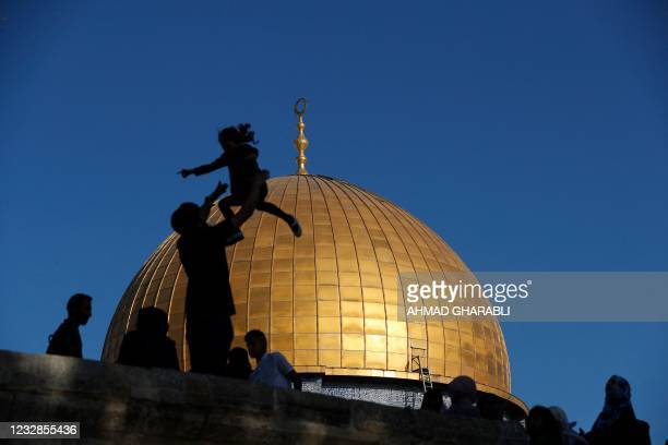 Muslim worshippers are silhouetted while celebrating in front of the Dome of the Rock mosque before the morning Eid al-Fitr prayer, which marks the...