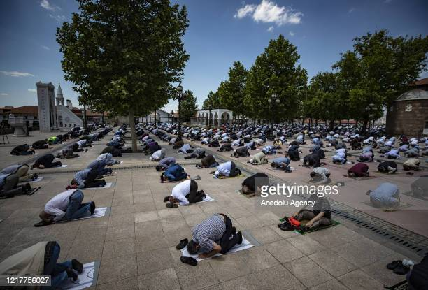 Muslim worshippers attend to perform Friday prayer while keeping social distance and wearing face masks at Haci Bayram Veli Mosque courtyard as...