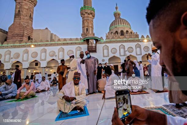 Muslim worshippers from Nigeria take pictures during Eid al-Fitr prayer, which marks the end of the holy fasting month of Ramadan, at al-Azhar mosque...