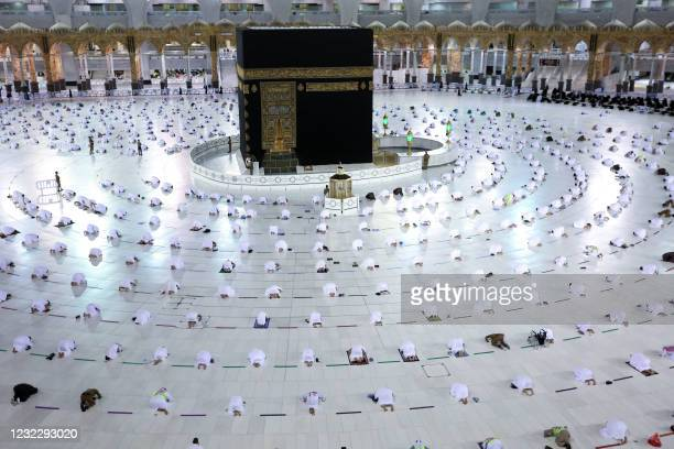 Muslim worshippers perform the evening Tarawih prayer during the fasting month of Ramadan around the Kaaba in the Grand Mosque complex in the holy...