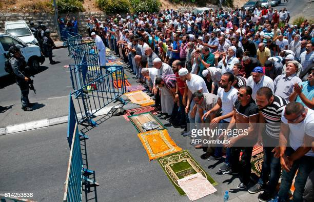 Muslim worshippers pray perform the traditional Friday prayers on a street outside the Lion Gate as Israeli police blocks the access to AlAqsa Mosque...