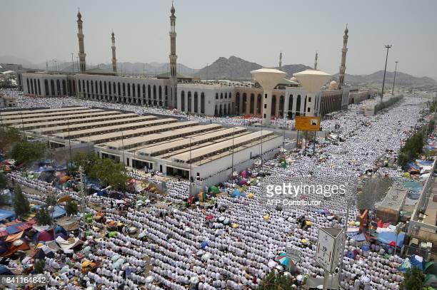 Muslim worshippers some carrying umbrellas to protect them from the scorching sun gather for prayer at Namirah mosque near Mount Arafat also known as...