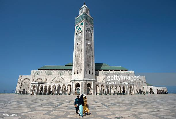 Muslim worshippers walk at the Hassan II mosque on September 6 2016 in the coastal Moroccan city of Casablanca Two months before it hosts the COP22...