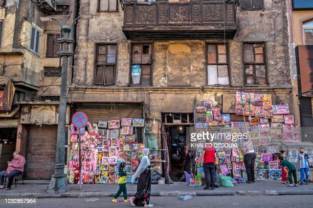 Muslim worshippers walk past a toy store following Eid al-Fitr prayers, which marks the end of the holy fasting month of Ramadan, at al-Azhar mosque...