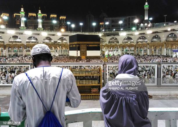 Muslim worshippers watch as others circumambulate around the Kaaba Islam's holiest shrine at the Grand Mosque in Saudi Arabia's holy city of Mecca on...