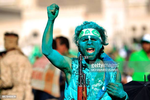Muslim Yemeni covered with green paint chants slogans as he attends a rally in the capital Sanaa on the occasion of the Prophet Mohammed's birthday...