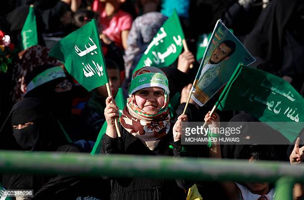 A Muslim Yemeni girls holds a flag bearing an image of Shiite Huthi leader AbdulMalik alHouthi and a flag bearing religious slogans during a rally on...