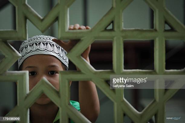 CONTENT] A muslim young boy is looking at the photographer through the mosque wall Kuala Lumpur Malaysia