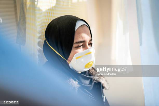 muslim young woman with protective mask outdoors - covid-19 stock pictures, royalty-free photos & images